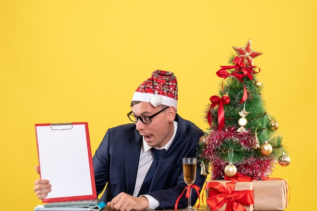 Vooraanzicht van zakenman kijken naar klembord zittend aan de tafel in de buurt van kerstboom en presenteert op geel