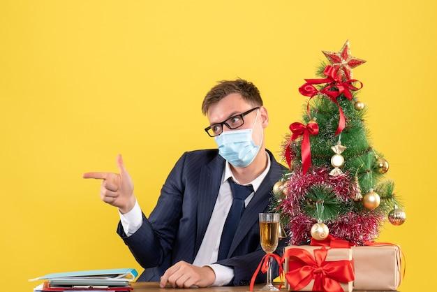 Vooraanzicht van zakenman met bril vinger pistool zitten aan de tafel in de buurt van kerstboom en presenteert op geel