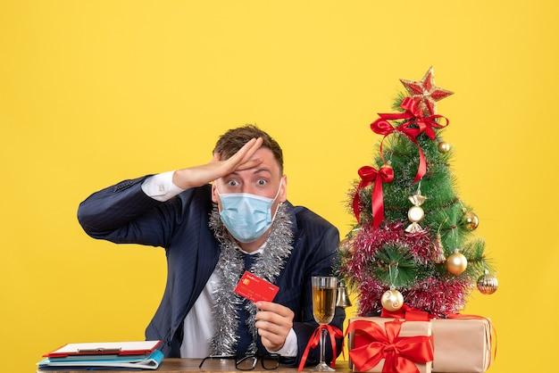 Vooraanzicht van zakenman met creditcard zittend aan de tafel in de buurt van kerstboom en presenteert op geel