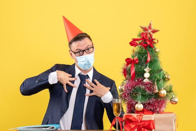 Vooraanzicht van zakenman met feestmuts zittend aan de tafel in de buurt van kerstboom en presenteert op geel