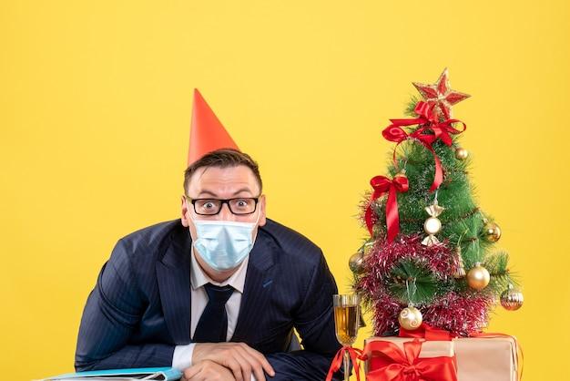 Vooraanzicht van zakenman met feestpet en masker zittend aan de tafel in de buurt van kerstboom en cadeautjes op geel