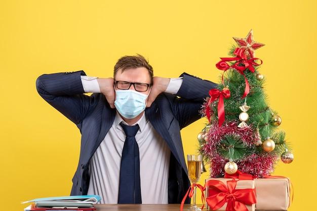 Vooraanzicht van zakenman met gesloten oog zijn oren sluiten met handen zittend aan de tafel in de buurt van kerstboom en presenteert op geel