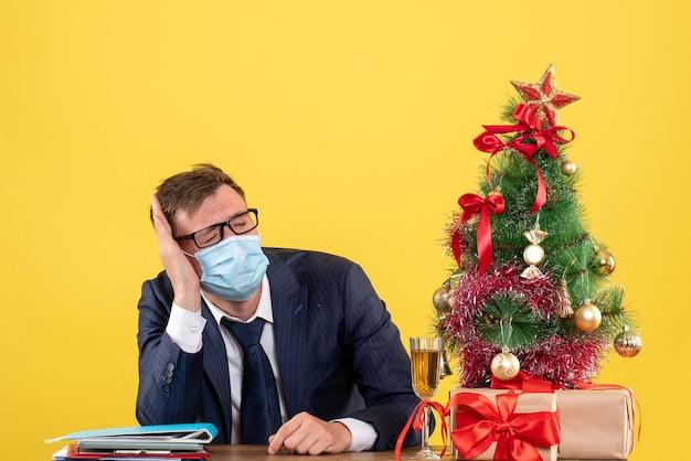 Vooraanzicht van zakenman met gesloten oog zittend aan de tafel in de buurt van kerstboom en presenteert op geel