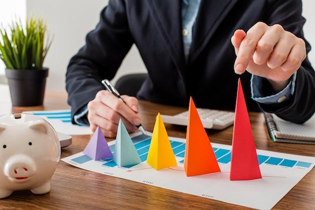 Vooraanzicht van zakenman met kleurrijke kegels die de groei vertegenwoordigen
