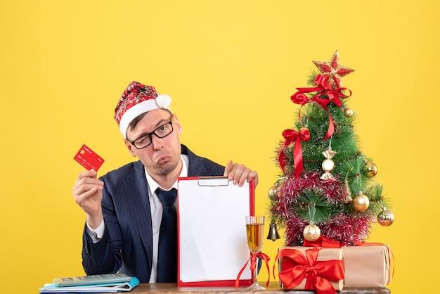 Vooraanzicht van zakenman met knipperend oog zittend aan de tafel in de buurt van kerstboom en presenteert op geel