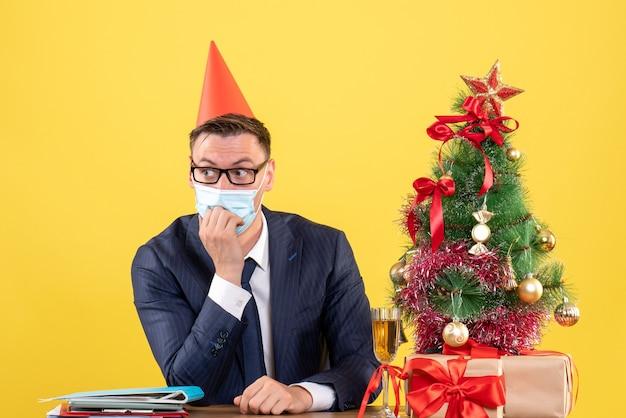 Vooraanzicht van zakenman met masker en feestmuts zittend aan de tafel in de buurt van kerstboom en presenteert op geel