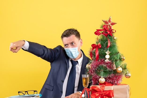 Vooraanzicht van zakenman met masker wijzend op iemand zittend aan de tafel in de buurt van kerstboom en presenteert op geel