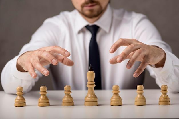 Vooraanzicht van zakenman met pionnen en koning