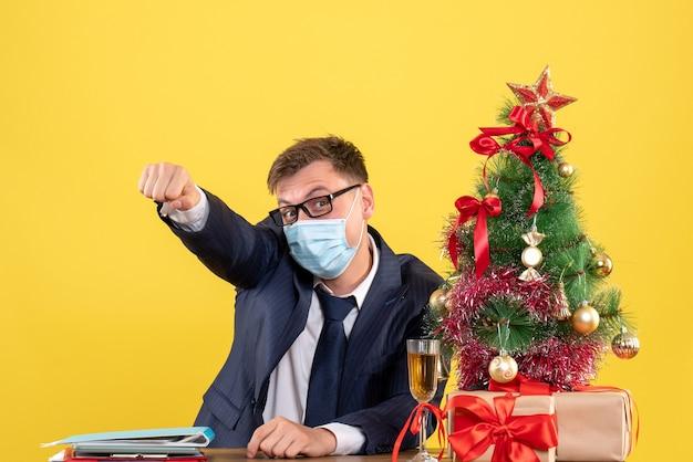 Vooraanzicht van zakenman verhogen zijn hand zittend aan de tafel in de buurt van kerstboom en presenteert op geel