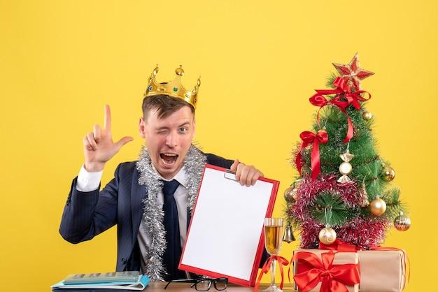 Vooraanzicht van zakenman vinger pistool zitten aan de tafel in de buurt van kerstboom en presenteert op geel