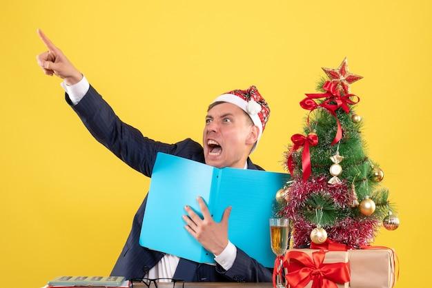 Vooraanzicht van zakenman wijzend met vinger iets met woede zittend aan tafel in de buurt van kerstboom en presenteert op geel