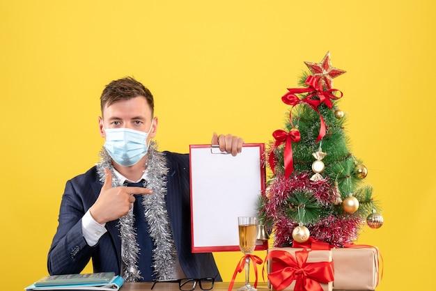 Vooraanzicht van zakenman wijzend op klembord zittend aan de tafel in de buurt van kerstboom en presenteert op geel
