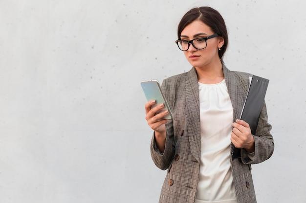 Vooraanzicht van zakenvrouw buitenshuis met smartphone en blocnote