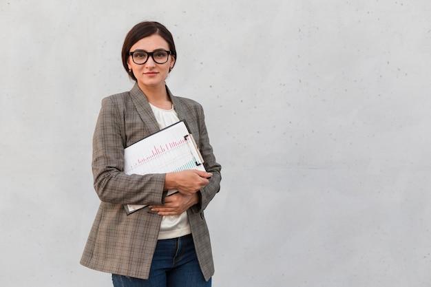 Vooraanzicht van zakenvrouw poseren buitenshuis met blocnote