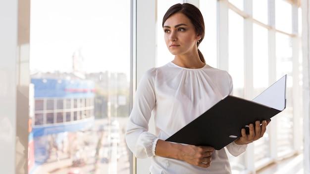 Vooraanzicht van zakenvrouw poseren met bindmiddel