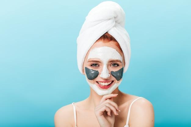 Vooraanzicht van zalige blanke vrouw met gezichtsmasker. studio shot van aangenaam meisje met handdoek op hoofd poseren op blauwe achtergrond.