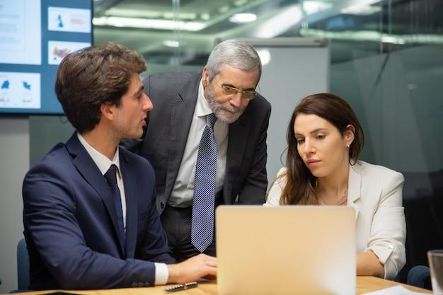 Vooraanzicht van zeker commercieel team dat laptop bekijkt