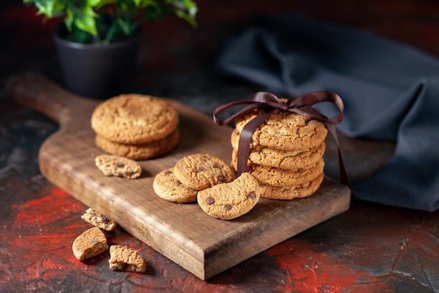 Vooraanzicht van zelfgemaakte heerlijke suikerkoekjes op een houten bord en bloempot op een donkere achtergrond van mixkleuren