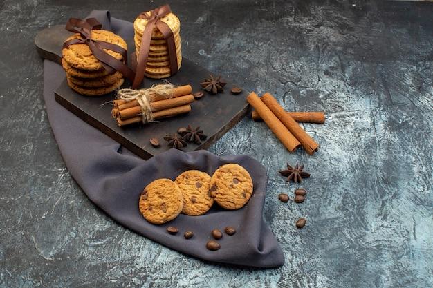 Vooraanzicht van zelfgemaakte koekjes kaneel limoenen op houten snijplank op donkere kleur handdoek op ijs achtergrond