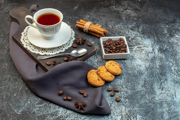 Vooraanzicht van zelfgemaakte koekjes, kaneellimoenen en een kopje thee op houten snijplankkoffiebonen op ijsachtergrond