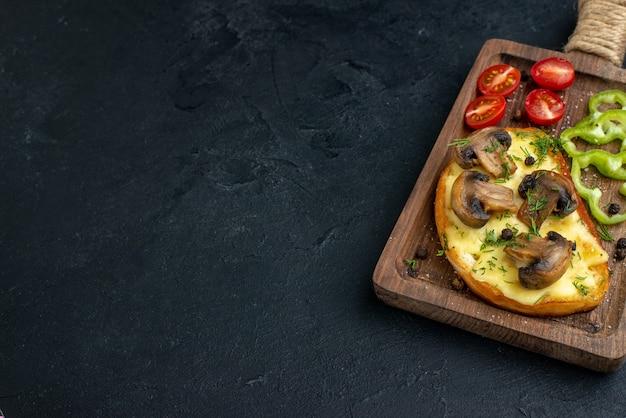 Vooraanzicht van zelfgemaakte smakelijke snack met champignons en gehakte groenten op een houten bord op zwarte achtergrond
