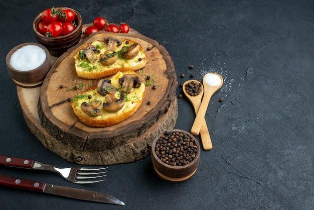 Vooraanzicht van zelfgemaakte smakelijke snack met champignons, tomaten, zout op houten bordbestek op zwarte achtergrond