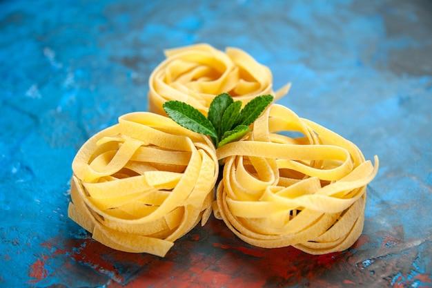 Vooraanzicht van zelfgemaakte verse tagliatelle-pasta's met groen op blauwe achtergrond