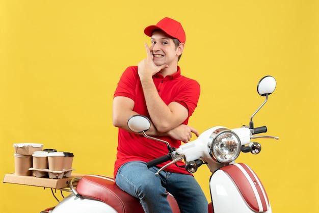 Vooraanzicht van zelfverzekerde gelukkige jonge kerel die rode blouse en hoed draagt die orden op gele achtergrond levert