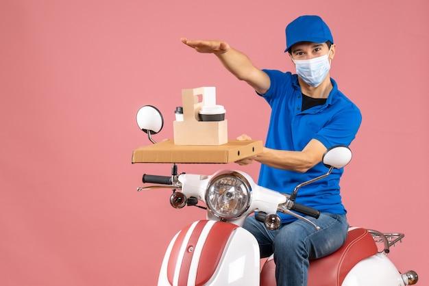 Vooraanzicht van zelfverzekerde glimlachende mannelijke bezorger in masker met een hoed die op een scooter zit en bestellingen aflevert op een pastelkleurige perzikachtergrond