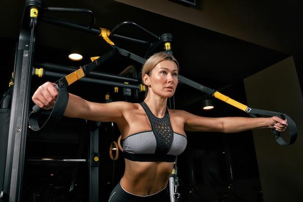 Vooraanzicht van zelfverzekerde jonge blonde vrouw die gewichtheffen training doet aantrekkelijke jonge vrouw die halters opheft die vooruit kijkt sterk getrainde lichaamsvorm armen borstbenen
