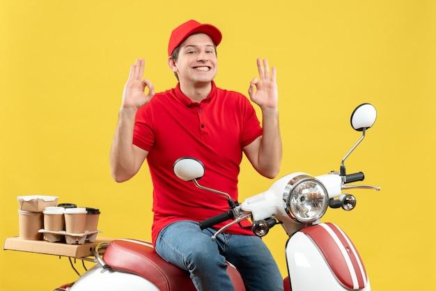 Vooraanzicht van zelfverzekerde jonge kerel die rode blouse en hoed draagt die orden levert die brillengebaar maken met beide kanten op gele achtergrond
