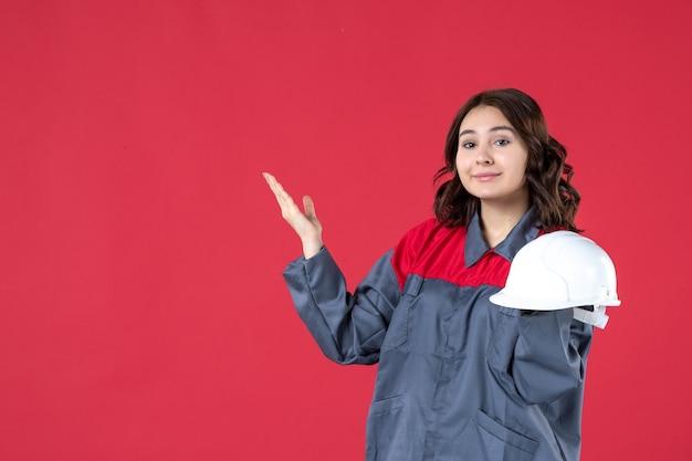 Vooraanzicht van zelfverzekerde vrouwelijke architect die bouwvakker houdt en aan de rechterkant op geïsoleerde rode muur benadrukt