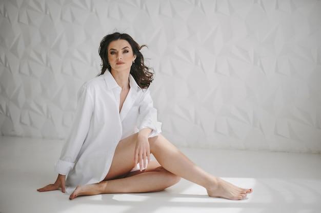 Vooraanzicht van zittend op de vloer, mooie jonge vrouw gekleed in een wit overhemd van een man, recht in een modern ingerichte kamer