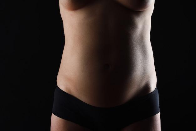 Vooraanzicht van zwangere buik naket op zwarte achtergrond