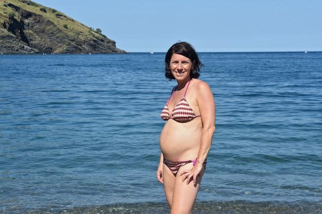 Vooraanzicht van zwangere vrouw die op het strand staat