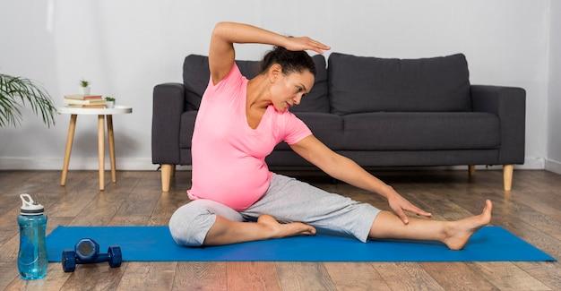 Vooraanzicht van zwangere vrouw die op mat thuis oefent