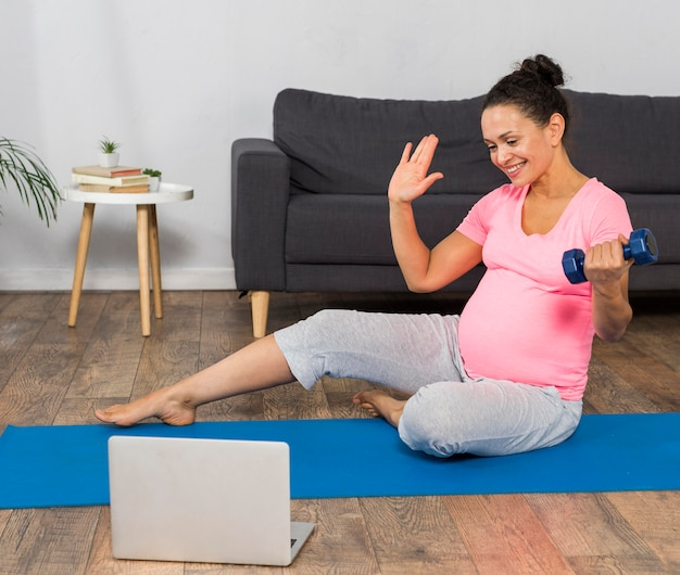 Vooraanzicht van zwangere vrouw die thuis op mat met laptop en gewicht uitoefent