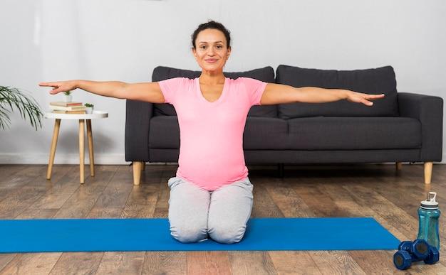 Vooraanzicht van zwangere vrouw die thuis op mat uitoefent