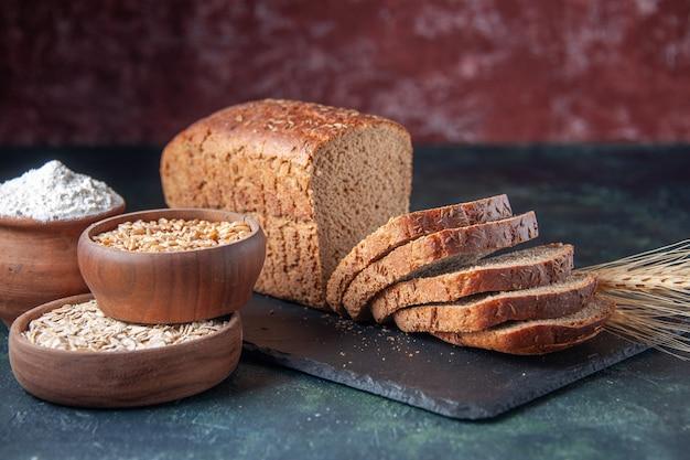 Vooraanzicht van zwart brood sneetjes meel havermout boekweit op donkere kleur bord op blauwe noodlijdende achtergrond