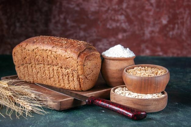 Vooraanzicht van zwart brood sneetjes meel in een kom op een houten bord en mes spikes rauwe havermout tarwe op gemengde kleuren noodlijdende achtergrond