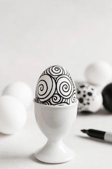 Vooraanzicht van zwart-wit ei voor pasen in eierdop met exemplaarruimte