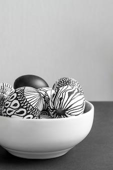 Vooraanzicht van zwart-wit eieren voor pasen in kom met exemplaarruimte