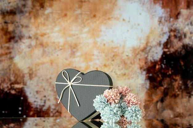 Vooraanzicht van zwarte hartdoos gekleurde bloemen op bruine abstracte achtergrondexemplaarplaats