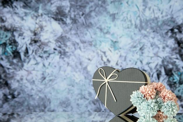 Vooraanzicht van zwarte hartdoos gekleurde bloemen op grijze abstracte achtergrond met vrije plaats