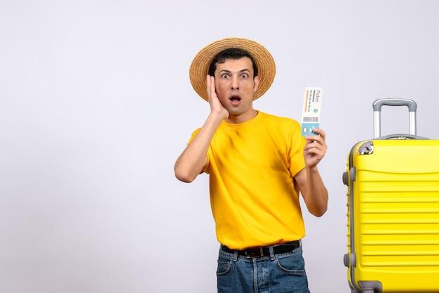 Vooraanzicht verbaasd jonge toerist in gele t-shirt staande in de buurt van gele koffer