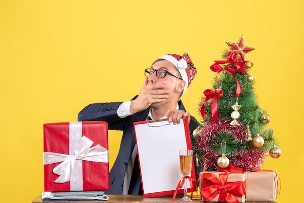 Vooraanzicht verbaasd man zittend aan de tafel in de buurt van kerstboom en cadeautjes op gele achtergrond vrije ruimte