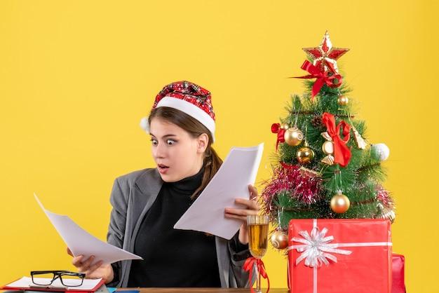 Vooraanzicht verbaasd meisje met xmas hoed zittend aan tafel kijken documenten kerstboom en geschenken cocktail
