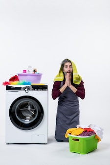 Vooraanzicht verbaasde huishoudster man die op de knie staat en de handen in elkaar steekt wasmand op witte muur