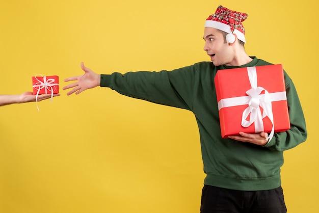Vooraanzicht verbaasde jonge man die het geschenk in vrouwelijke hand probeert te vangen die op geel staat
