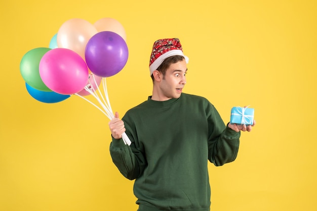 Vooraanzicht verbaasde jonge man met kerstmuts en kleurrijke ballonnen staande op geel